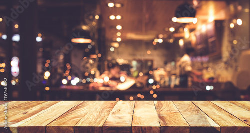 Wood table top (Bar) with blur night cafe background