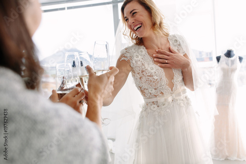 Photo Bride toasting champagne with friends in bridal boutique