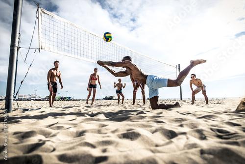 Fototapeta premium Grupa przyjaciół grających w siatkówkę plażową na plaży.