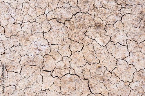 Brown dry soil or cracked ground texture background. Fototapet