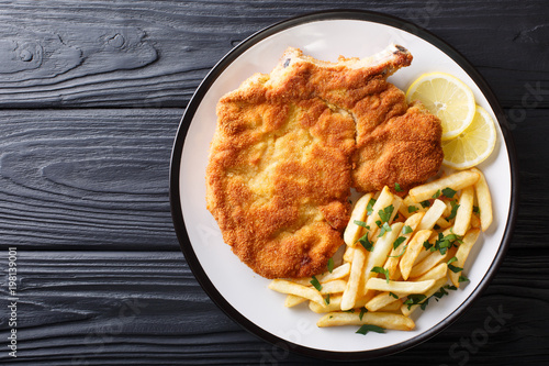 Obraz na plátně Traditional Italian veal Milanese with lemon and French fries close-up