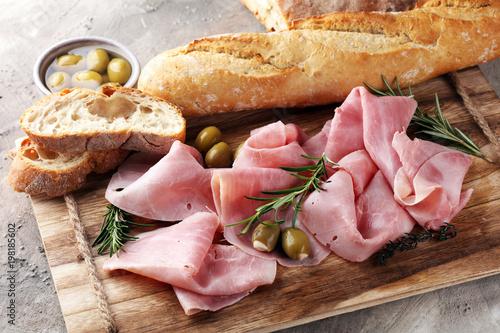 Sliced ham on wooden board. Fresh prosciutto. Pork ham sliced.