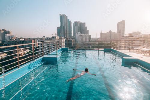 Fototapeta premium Kobieta pływanie w basenie na dachu