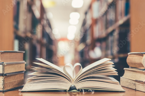 Love story book with open page of literature in heart shape and stack piles of textbooks on reading desk in library study room for education learning, and national library lovers month concept
