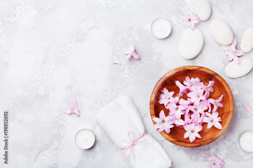 Spa, aromatherapy, beauty background with massage pebble, perfumed flowers water and candles on stone table from above. Relaxation and zen like concept. Flat lay.