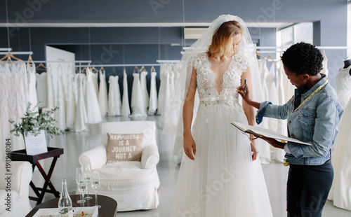 Foto Dress designer fitting bridal gown to woman in boutique