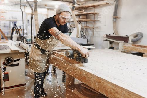 Billede på lærred Carpenter working with electric planer on wooden plank in workshop