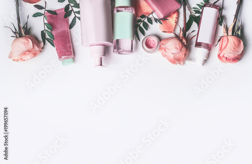 Cosmetics set with Rose essential oils: toner,serum, essence,moisturizer and and others on white desktop background, top view, border. Facial Skin care beauty treatment