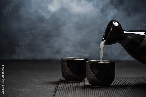 Pouring sake into sipping ceramic bowl