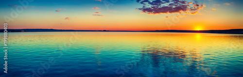 Zachód słońca nad jeziorem. Niesamowity krajobraz panoramy