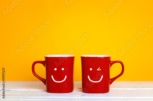 Two red coffee mugs with a smiling faces on a yellow background with copy space.