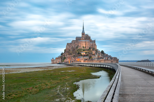 Fototapeta Beautiful famous Mont Saint Michel with bridge and reflection in the canal at lo