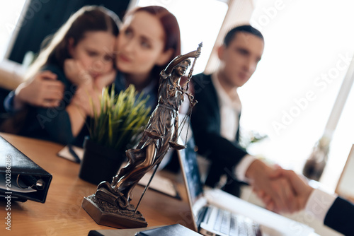 Fotografija Bronze statue of Themis stands on table, behind which sits divorcing parents with little girl
