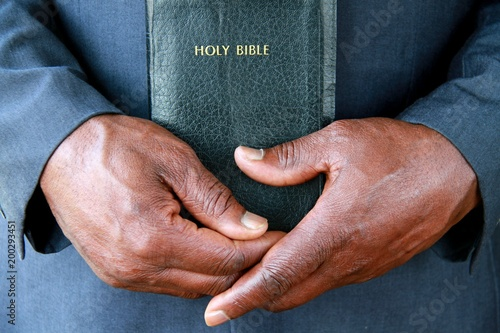 Wallpaper Mural Caribbean man holding Bible in church after ceremony stock photo