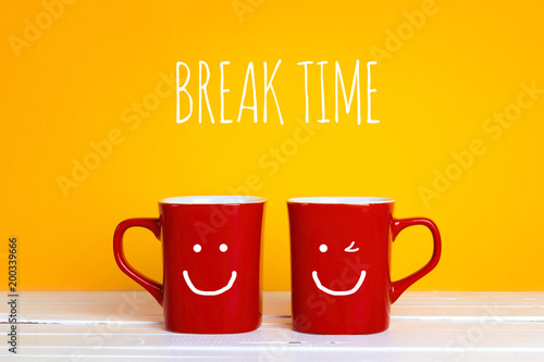 Two red coffee mugs with a smiling faces on a yellow background with the phrase Break time.