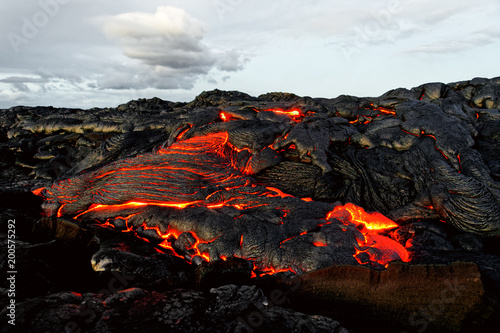 """A lava flow emerges from an earth column and flows in a black volcanic landscape, in the sky shows the first daylight - Location: Hawaii, Big Island, volcano """"Kilauea"""""""
