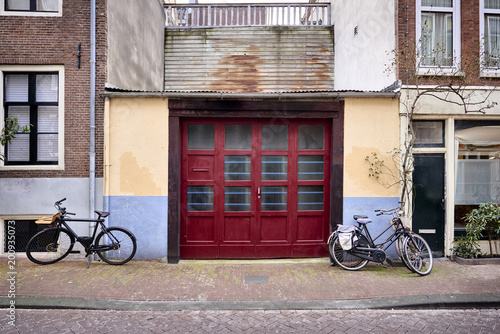 a vibrant red garage door on an old building with bicycles parked on the street.