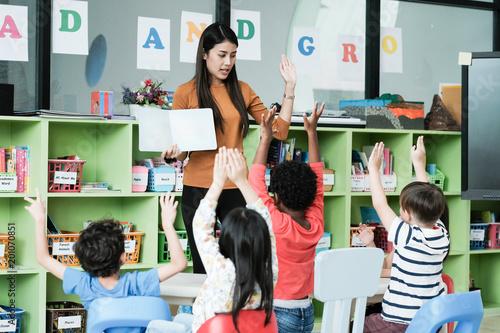 Obraz na plátně Young asian woman teacher teaching kids in kindergarten classroom, preschool edu