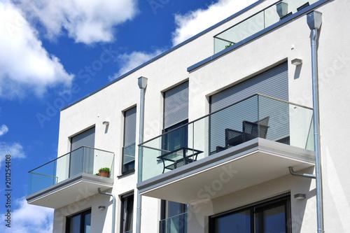 Moderne Balkone, verglast mit Metall-Geländer an Neubau-Hausfront mit Flachdach, Fototapete