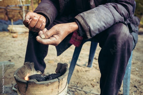 Carta da parati portrait old man on rural of Thailand in winter season with the small fireplace