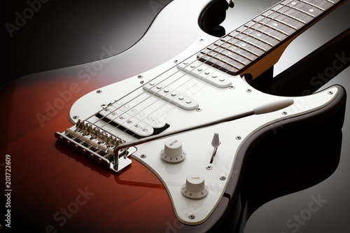 Canvas Print Close up on the body of elegant electric guitar with sunburst finish, black glos