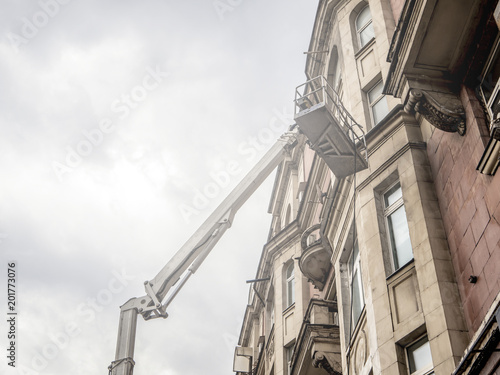 Leinwand Poster lifting crane with basket repairing architecture facade against the sky