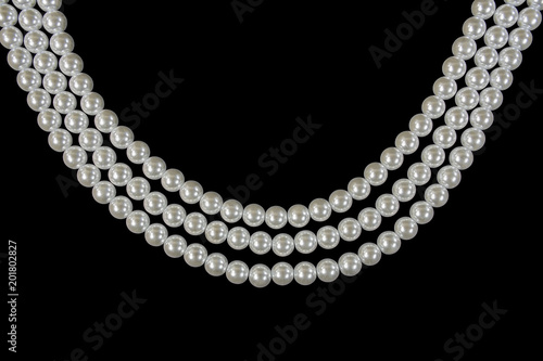 three strand pearl necklace on black background