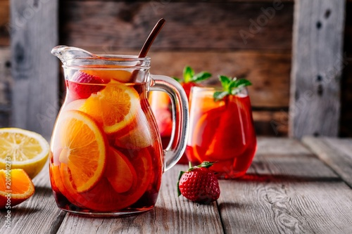 Fotografia Homemade red wine sangria with orange, apple, strawberry and ice in pitcher  and