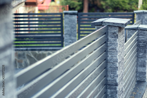 Fotografie, Tablou Modern fence with stone pillars and metal filling
