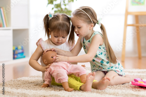 Fotografia Two children girls playing doctor with a doll in kindergarten