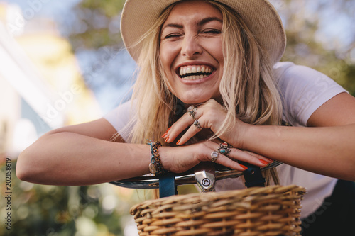 Stampa su Tela Attractive woman laughing outdoors with her bike