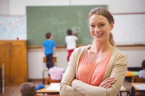 Canvas Print Pretty teacher smiling at camera at back of classroom
