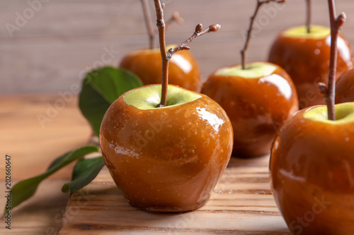 Delicious green caramel apples on table