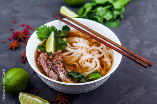 Vietnamese Pho Noodle Soup. Beef with Chilli, Basil, Rice Noodles, Bean Shoots showing noodles