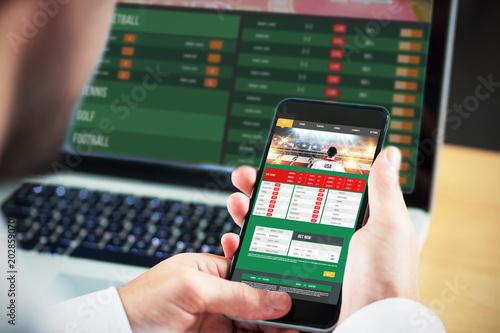 Fotografija Businessman using smartphone against gambling app screen