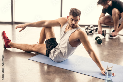 Fotografia handsome sportsmen stretching on yoga mat in gym