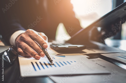 Close up Businessman consultant holding pen and pointing at financial on wooden desk in coffee shop Fototapeta