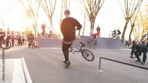 Valokuva BMX rider with a bike performs stunts in a skate park in the background of cyclists and sunset