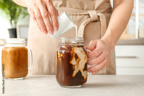 Woman pouring milk into mason jar with cold brew coffee on table Poster Mural XXL