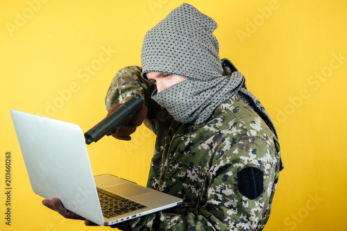 Wallpaper Mural Portrait of a hacker man terroris in a camouflage and a mask is looking at the laptop