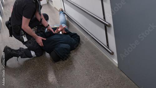 Obraz na płótnie Prison guard right inmate resisting arrest in prison after commiting crime