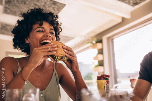 Canvas Print Woman enjoying eating burger at restaurant