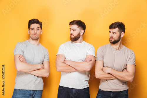 Two young upset men looking at their male friend Fototapeta