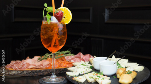 Traditional italian aperitif with proscioutto, mortadella sausage, cheese and aperol spritz drink