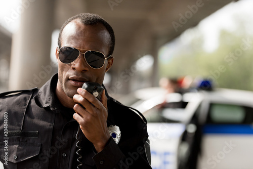 Carta da parati african american police officer talking by walkie-talkie radio set