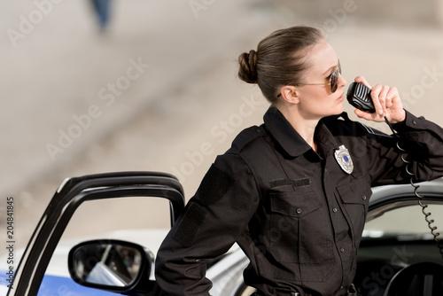 Obraz na płótnie young policewoman in sunglasses talking on portable radio