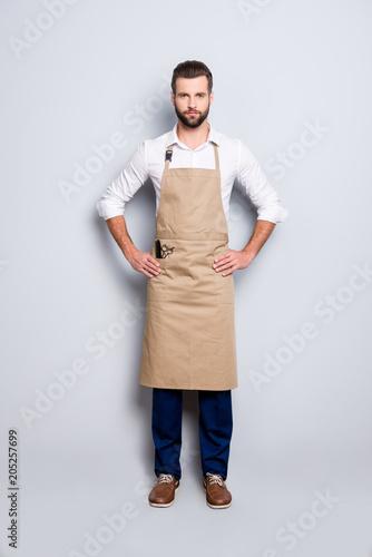 Fotografia Full size fullbody portrait of virile harsh barber in uniform holding arms on wa