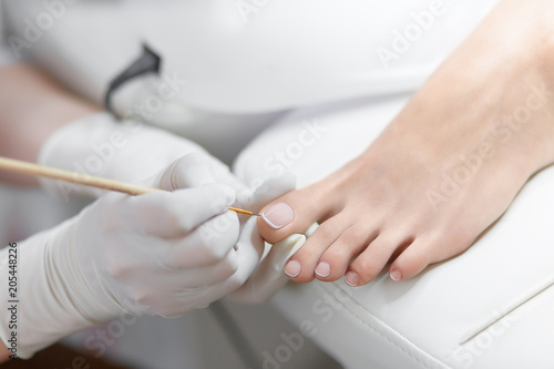 Specialist in beauty salon making french pedicure for female client.