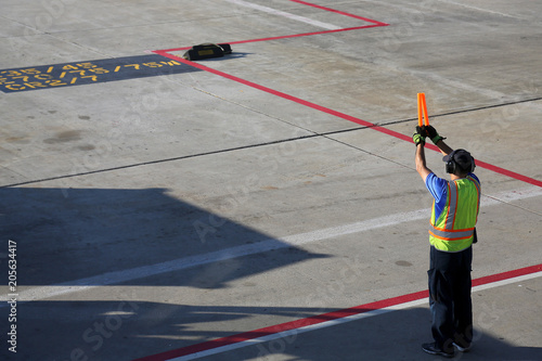 Fotomural Ground crew signaling to incoming taxing airplane arriving for a spot at the terminal