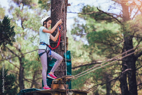 Canvas Print Happy school girl enjoying activity in a climbing adventure park on a summer day